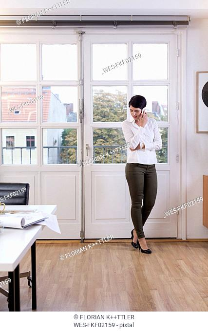 Woman standing at the window in office talking on phone