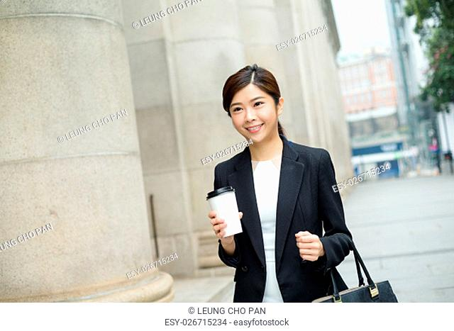 Business woman walking outside and drinking coffee