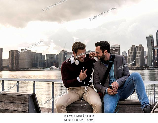 USA, New York City, two happy young men with headphones and cell phone sitting at East River