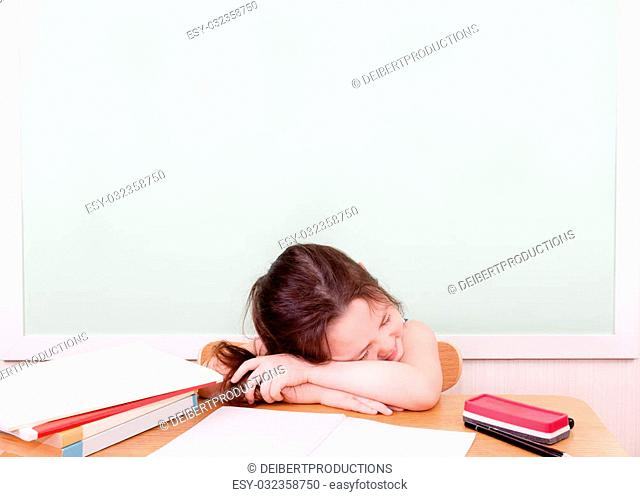 A young student is sleeping at her desk