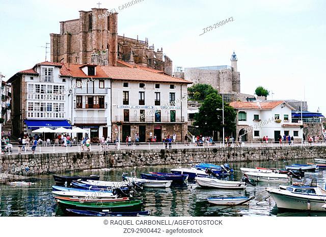 Santa María de la Asunción church and the lighthouse of the Castle of Santa Ana people walking on promenade and moored boats, Castro Urdiales, Cantabria, Spain