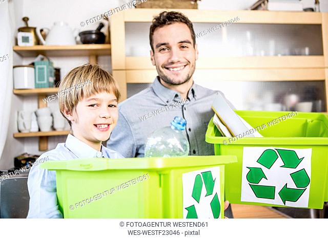 Father and son at home with waste boxes