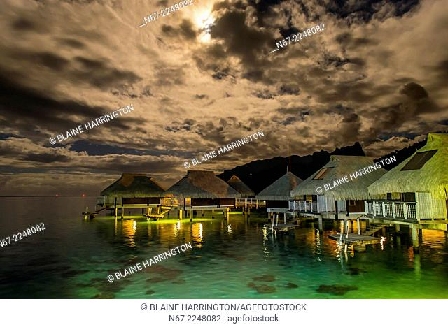 Overwater bungalows at night in the moonlight, Hilton Moorea Lagoon Resort, island of Moorea, French Polynesia
