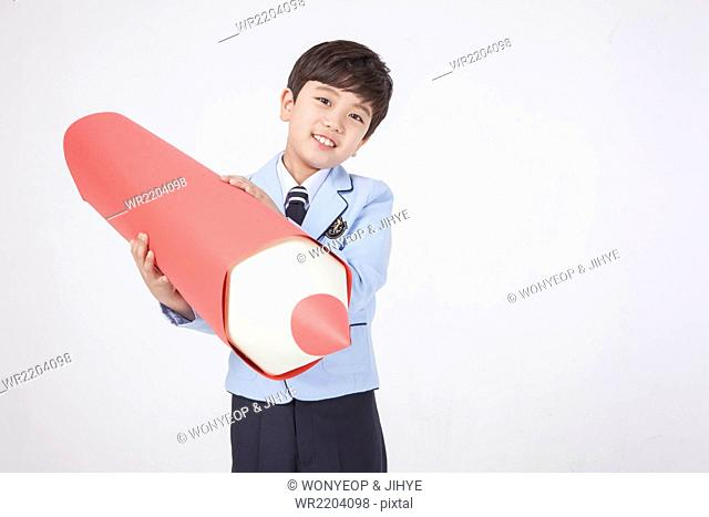 Elementary school boy in school uniforms holding a big red pencil
