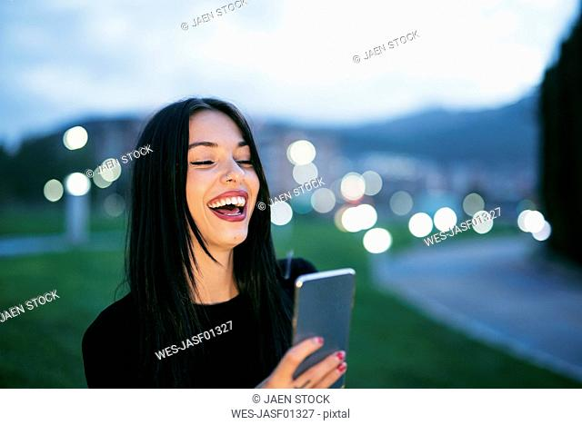 Portrait of laughing young woman with smartphone