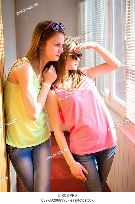 Closeup picture of two pretty teenage girls wearing sunglasses belly shirts and jeans having fun in sunroom looking over blinds on sunny day