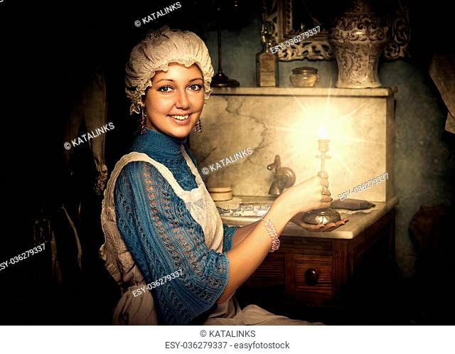 Retro portrait of beautiful woman in old cap with candlestick