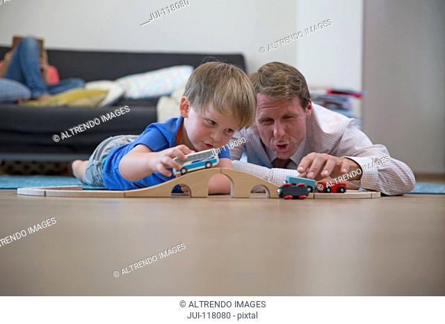 Father And Son Playing With Toy Cars At Home