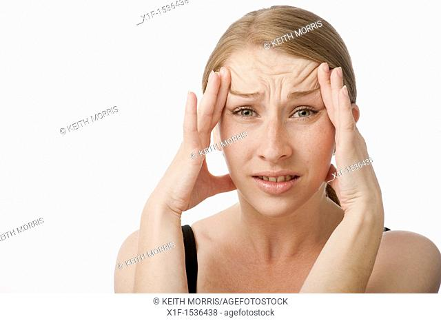 a young caucasian woman with a headache rubbing her forehead to relieve the pain, UK