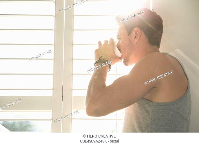 Young man drinking coffee and looking through sunlit bedroom window in morning