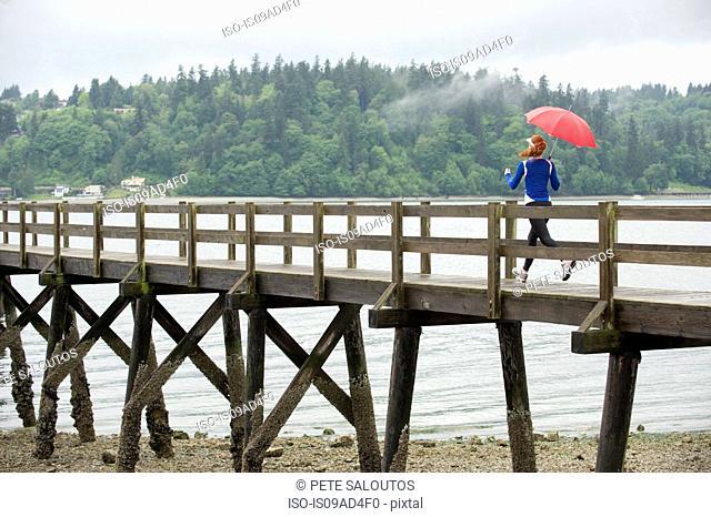 Teenage girl running with umbrella on pier, Bainbridge Island, Washington, USA