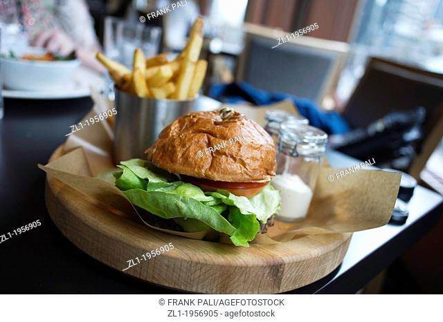 Close up of a Hamburger on wood plate shallow depth of field