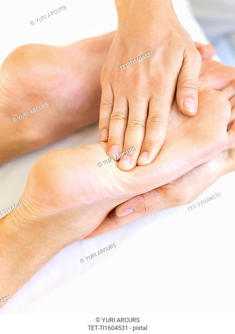 Hand massaging feet