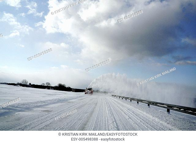 Snowblower clears the road. Clouds and snow. Denmark