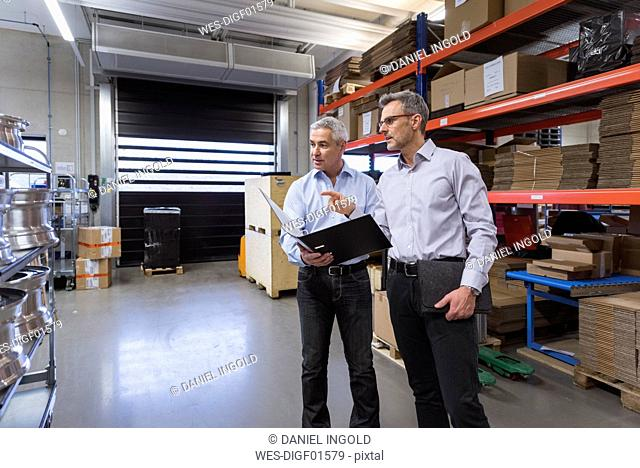Two businessmen in factory hall talking