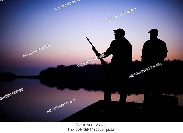 Silhouette of two hunters on jetty at sunset