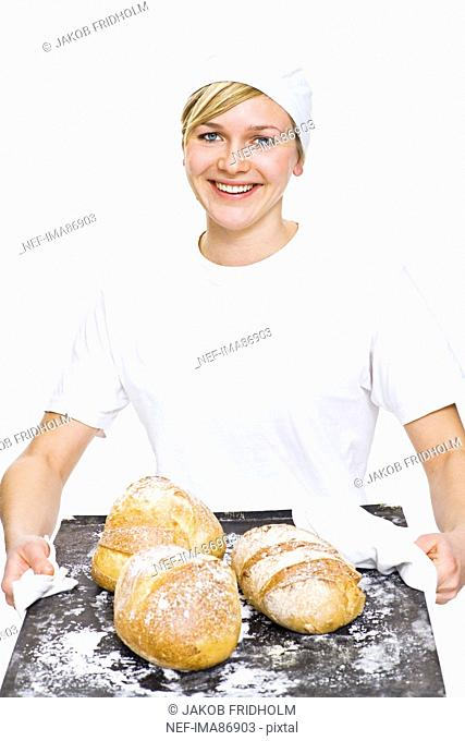 Woman holding baking tray with bread, smiling, portrait