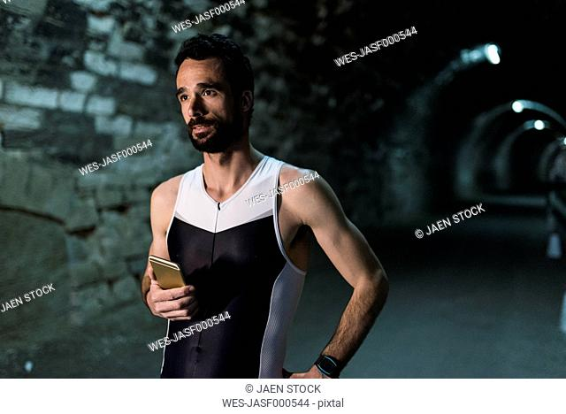 Portrait of runner with smartphone in a tunnel