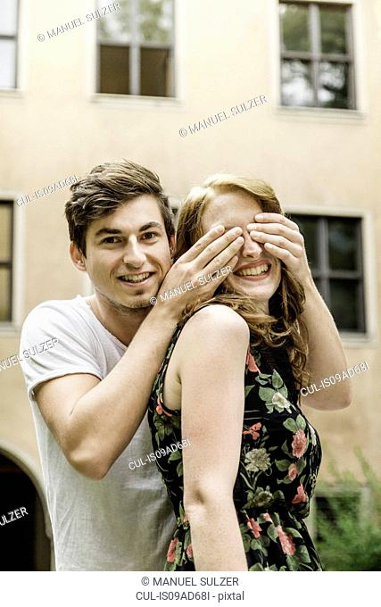 Young man covering girlfriend's eyes