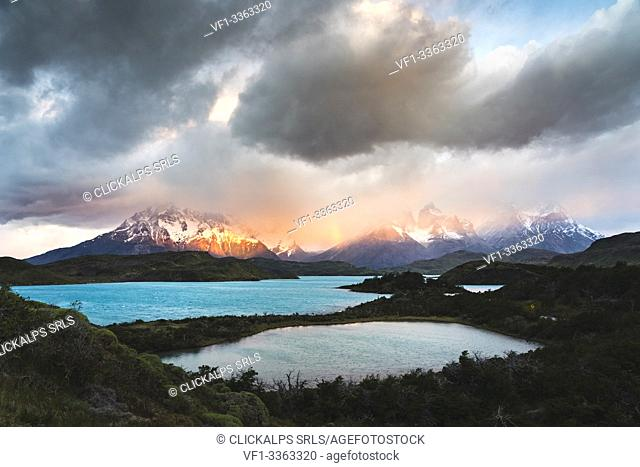 Pehoé Lake and rainbow at dawn, with Cerro Paine Grande, Paine Horns and Cerro Paine covered in mist in the background. Torres del Paine National Park