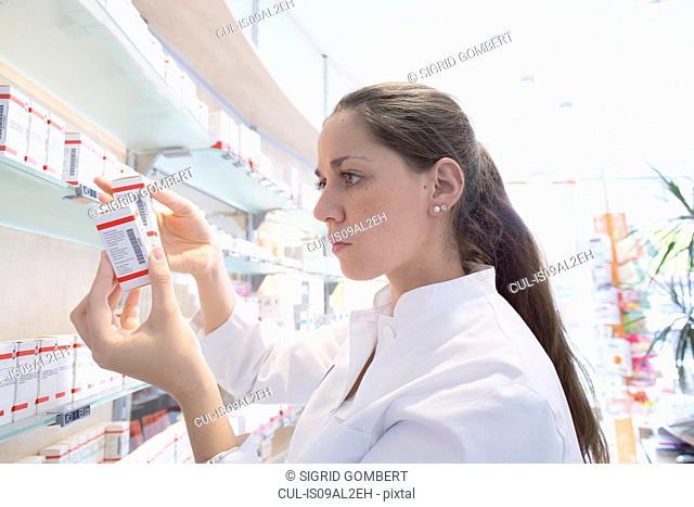 Pharmacist in pharmacy reading medicine box