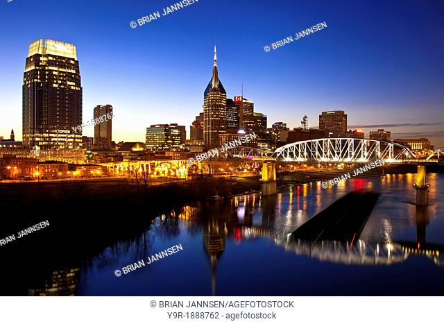 Coal barge on the Cumberland River and the town of Nashville Tennessee, USA
