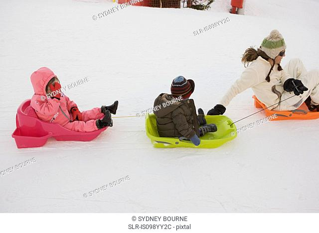 Mother pulling two children on sledges