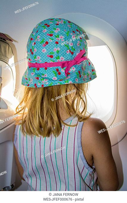 Little girl looking through window on board of an airplane