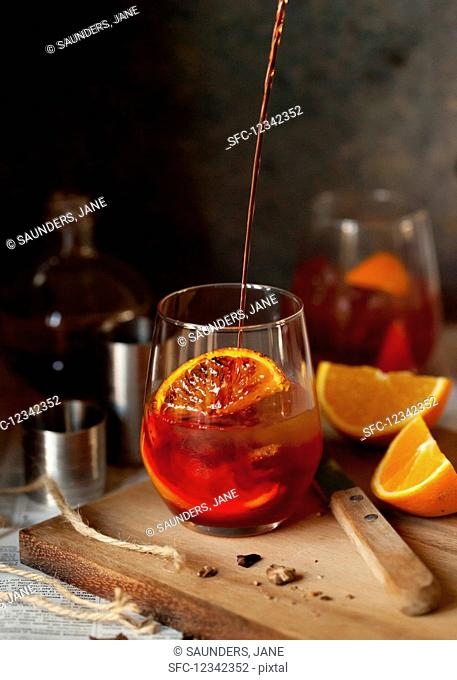 A Negroni cocktail being poured into a glass