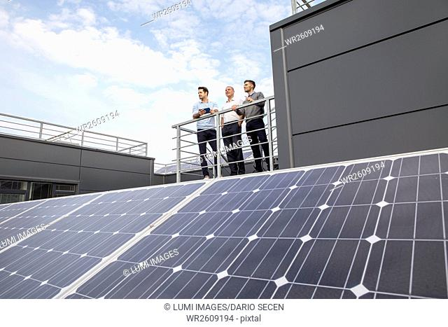 Group of business people looking at solar panels on rooftop