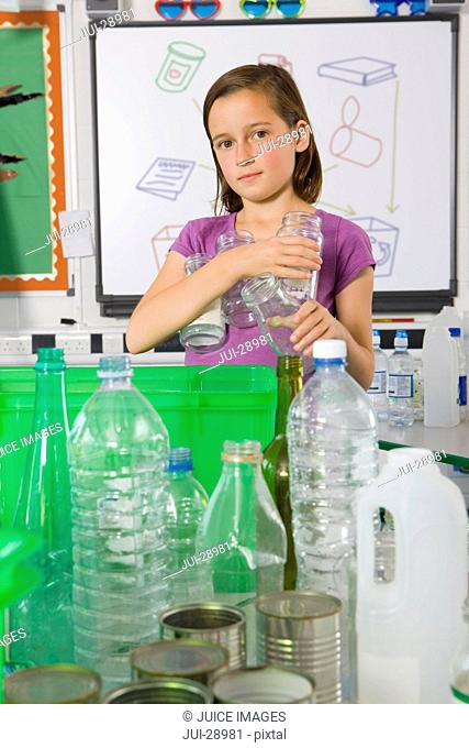 Serious student putting glass into recycling bin