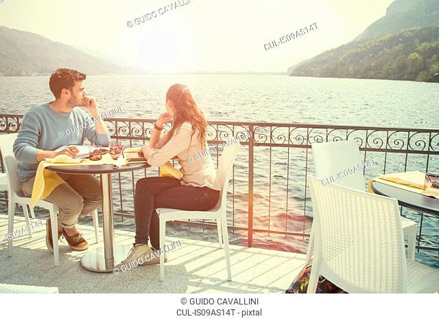 Couple looking out from lakeside restaurant, Lake Mergozzo, Verbania, Piemonte, Italy