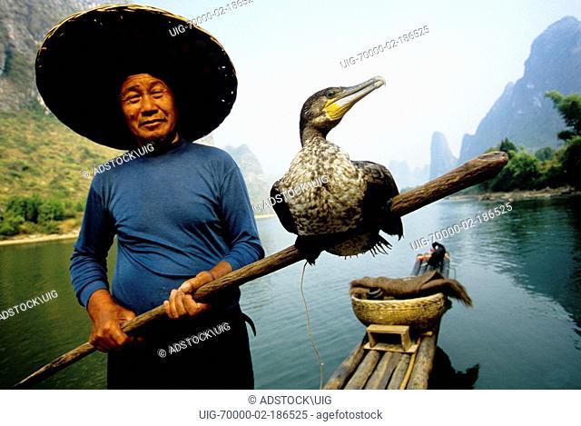 Fisherman on Li River on bamboo raft near Xingping Guilin area, Guangxi, China