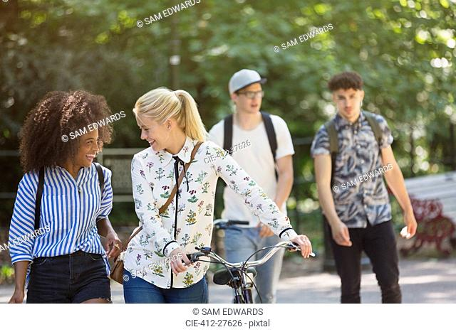 Friends walking with bicycle in park