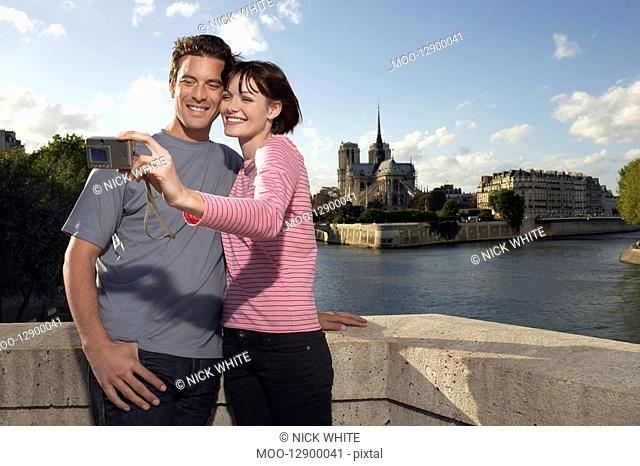 Paris France Couple taking a photo of themselves in front of Notre Dame Cathedral