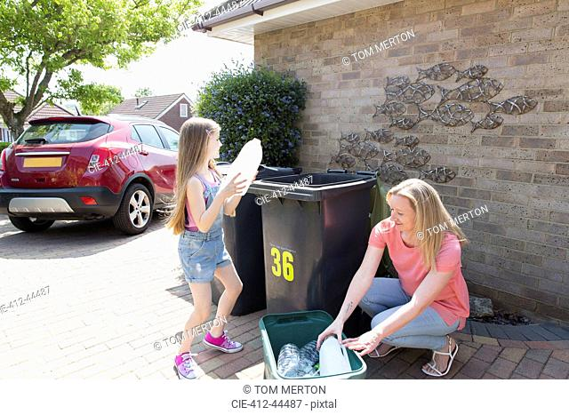 Mother and daughter recycling plastic outside house