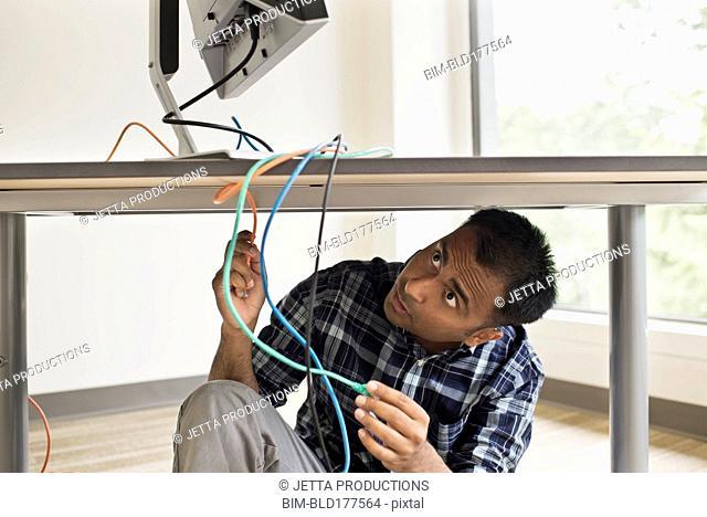 Mixed race businessman repairing computer