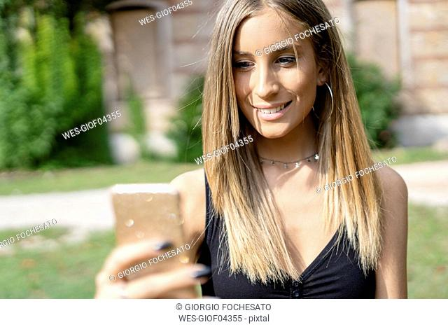 Smiling teenage girl using cell phone outdoors