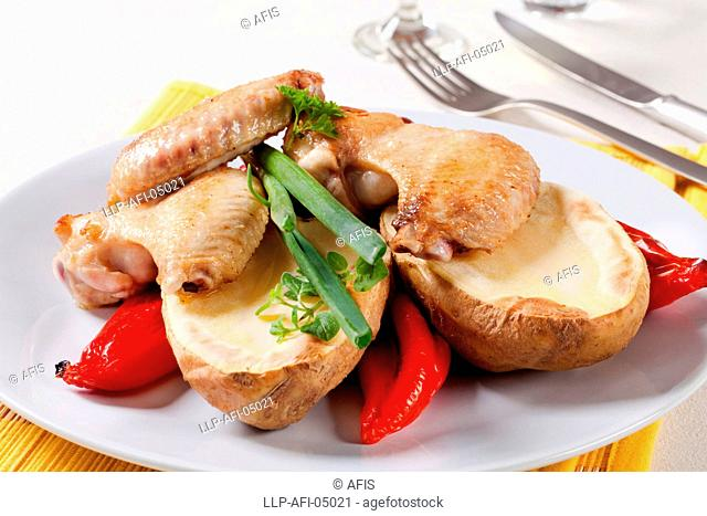 Roasted chicken wings with baked potato and red peppers