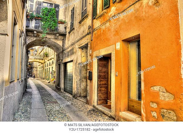 Old colorful stone alley with arches in orta italy