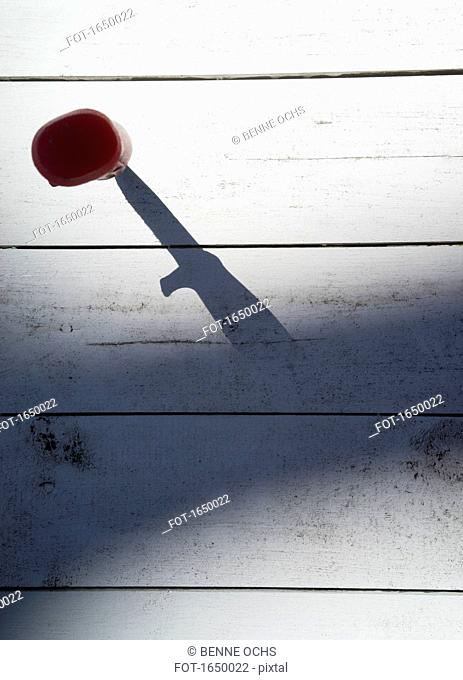 Directly above shot of knife on wooden table in shadow
