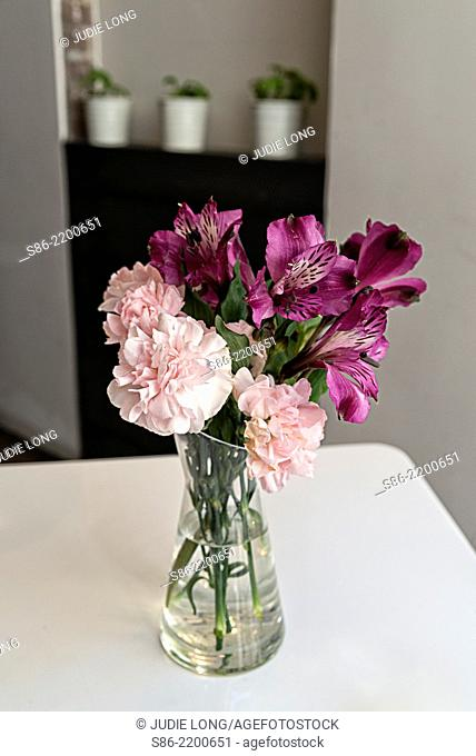 Carnations and Dark Pink Flowers in a Clear Glass Vase. Placed on a table in a New York City Restaurant