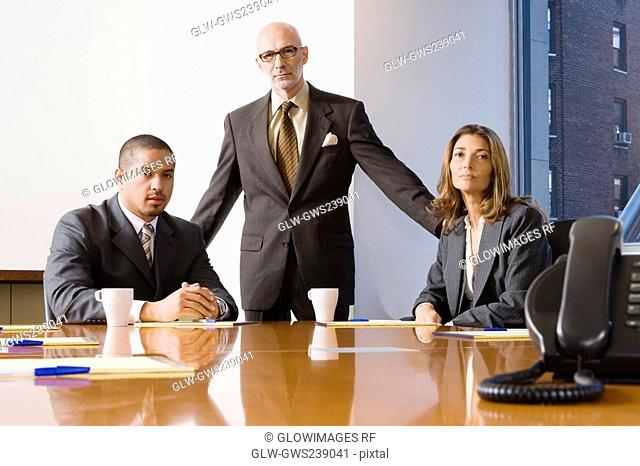 Portrait of two businessmen with a businesswoman in an office