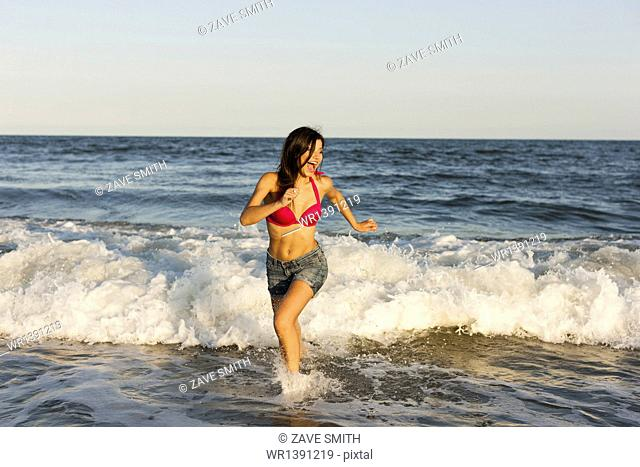 A beautiful young women at the water's edge on the beach in Atlantic City