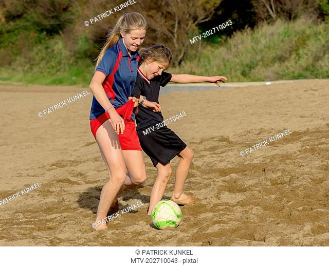 Two girls playing with soccer ball on the beach