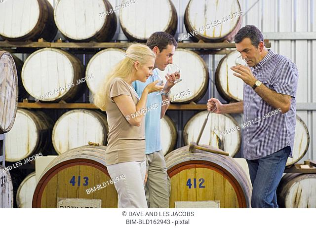 Caucasian friends tasting wine in winery