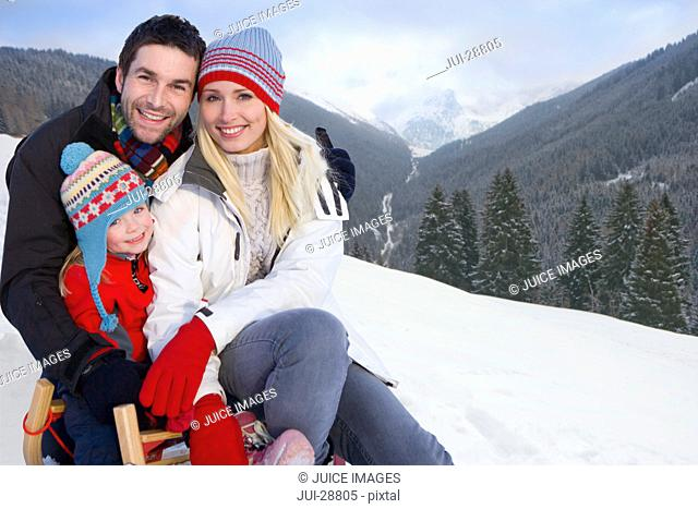 Smiling family sitting on remote snowy hillside together