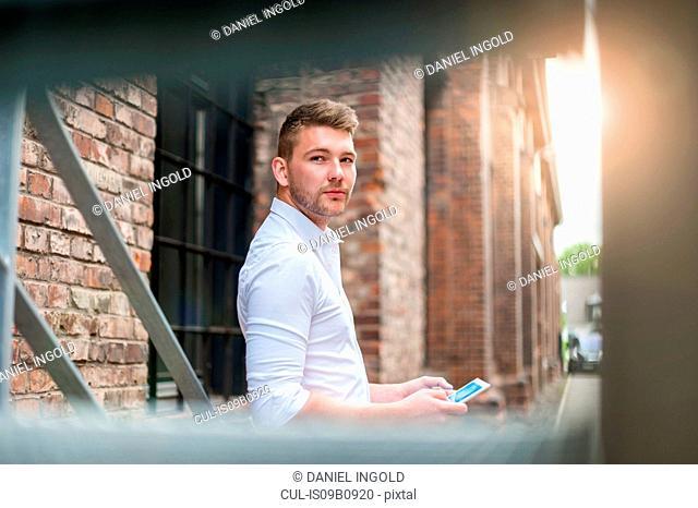 Young man using digital tablet beside brick building