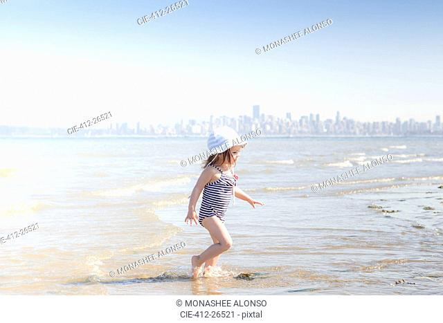 Girl wading in surf on beach