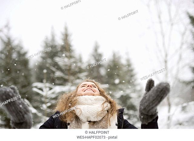 Happy young woman enjoying snowfall in winter forest